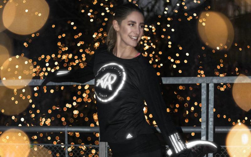 Adidas Runners Club Zürich Mädchen dehnen vor einem Lauf im Dunkeln Glitzern Goldhintergrund