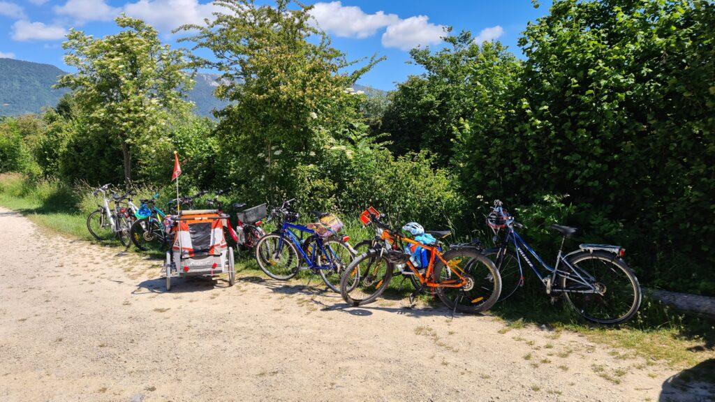 Pause auf einer Velotour mit Kindern: Kindervelos, Veloanhänger, Trailerbikes und Erwachsenenvelos stehen am Wegrand vor grünen Sträuchern.