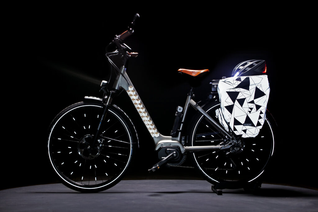 Ein silbriges E-Bike mit reflektierenden Hinterradtaschen, Speichenclips und reflektierendem Muster auf dem Rahmen