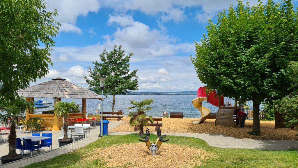Balade familiale à vélo autour du lac de Sempach, dans le canton de Lucerne: vue sur l'aire de jeux et la rive du lac depuis le restaurant Seeland de Sempach
