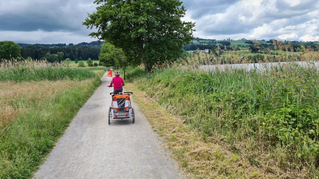 Balade familiale à vélo autour du lac de Sempach, dans le canton de Lucerne: un vélo équipé d'une remorque pour enfant longe la rive du lac de Sempach.