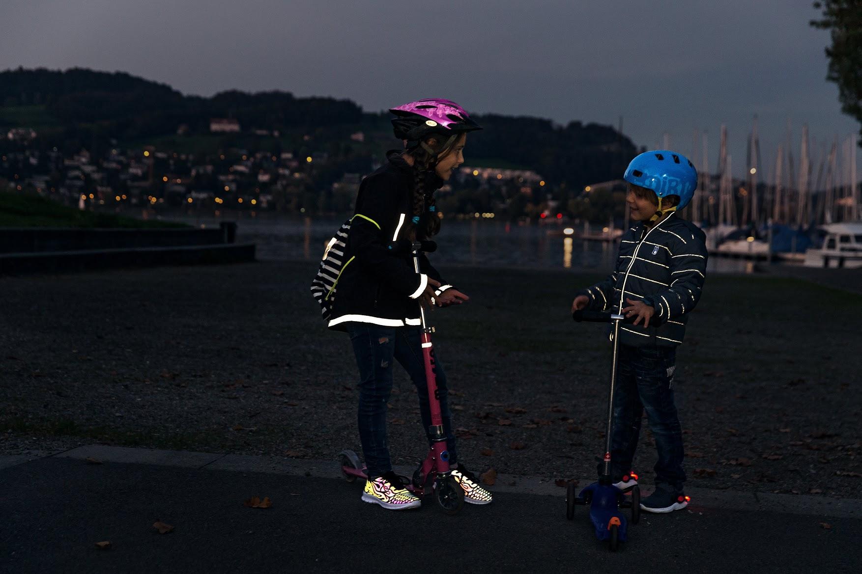 Sicurezza lungo il tragitto casa-scuola: due bambini con indumenti e accessori riflettenti