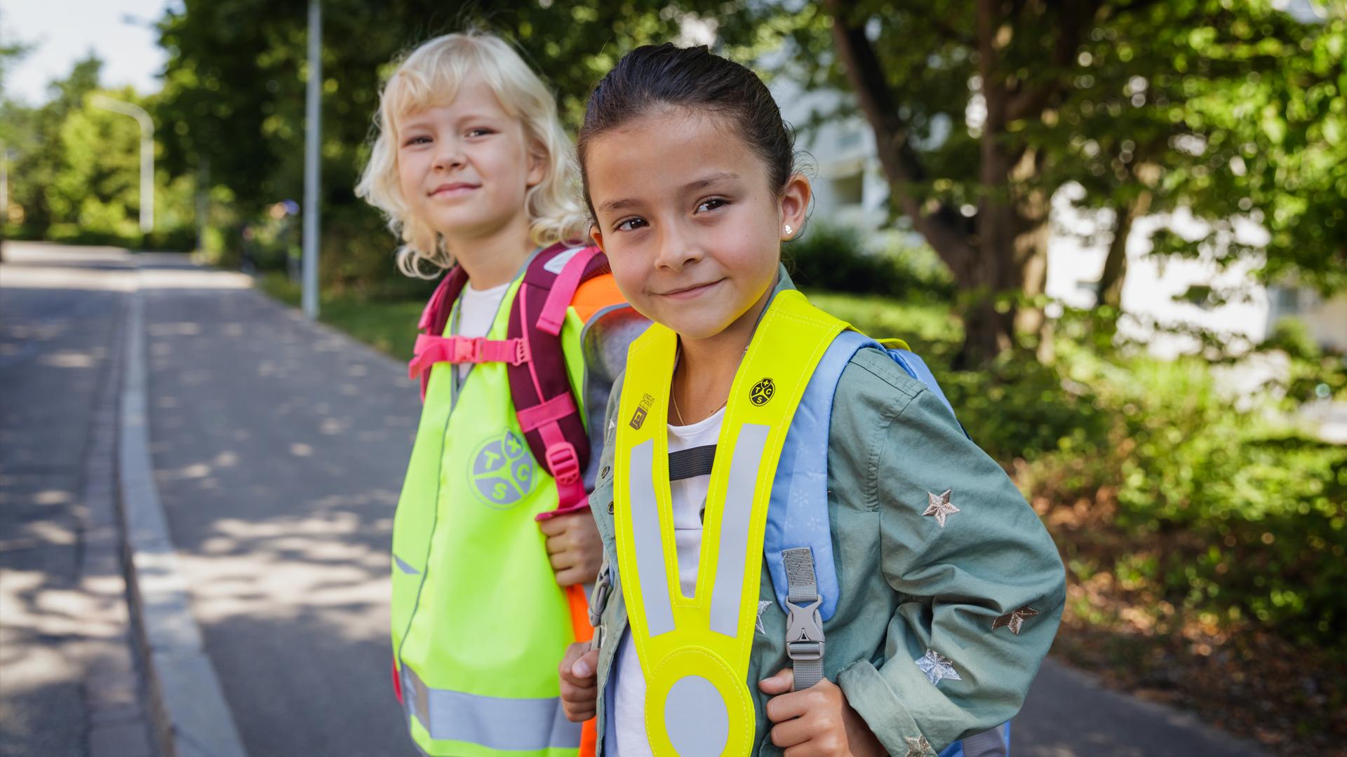Sicurezza nel tragitto casa-scuola: due bambine con gilet riflettente e pettorina catarifrangente (triki)
