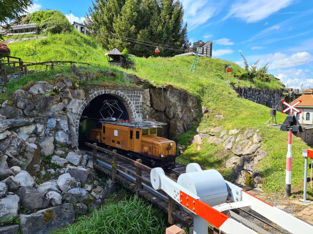 Originalgetreuer Modelnachbau des rhätischen Krokodils Ge 6/6 fährt durch den Swiss Vapeur Park bei Bouveret.