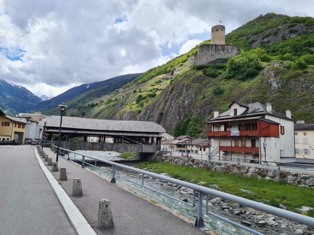 Burg La Bâtiaz auf dem Felsen oberhalb der Holzbrücke über den Fluss Dranse bei Martigny. Teil der Rhone-Route für Velos.
