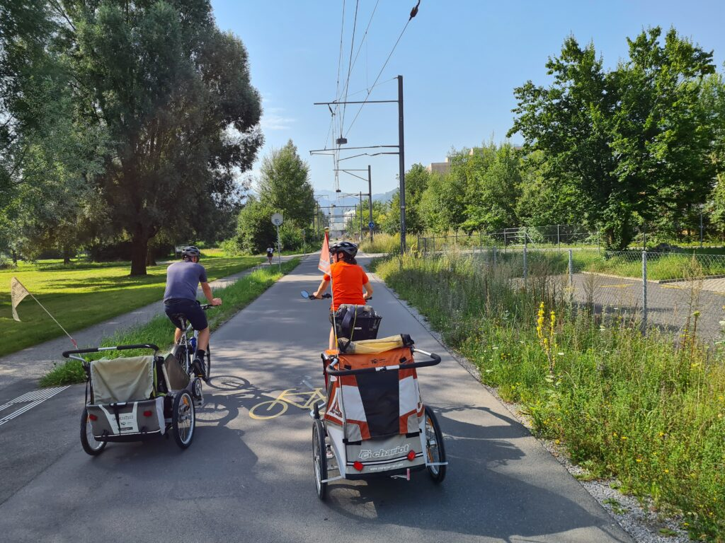 Tour in bicicletta nella Svizzera centrale: due ciclisti con rimorchietto pedalano sul Freigleis nei pressi di Lucerna. In alto si vedono le vecchie linee elettriche, a sinistra l'Allmend di Lucerna.