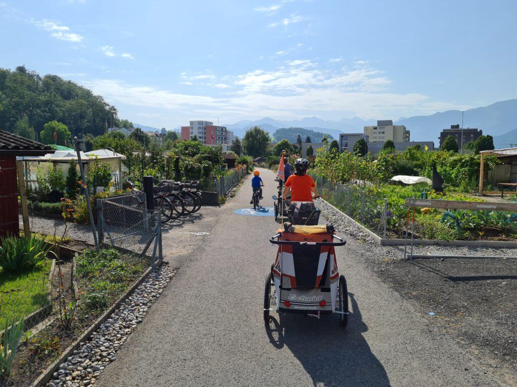Tour in bicicletta nella Svizzera centrale: un bambino e due adulti con rimorchietto transitano con le loro bici per gli orti dell'Allmend di Lucerna.