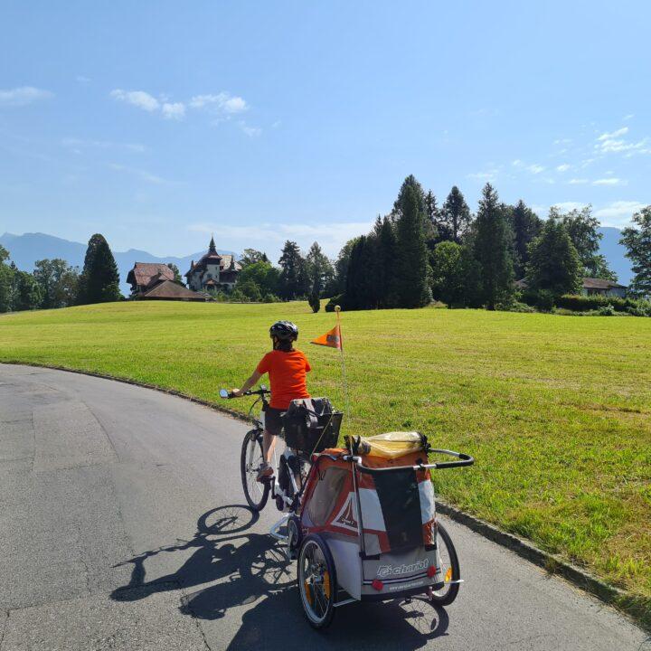Tour in bicicletta nella Svizzera centrale: una persona pedala con rimorchietto e bimbo al seguito presso St. Niklausen in direzione Lucerna. Sullo sfondo si intravede una villa su un prato verde.