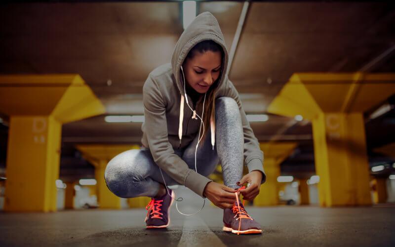 La coureuse fait ses lacets et se prépare à s'entraîner à la course à pied. Elle a des écouteurs dans l'oreille et écoute de la musique.