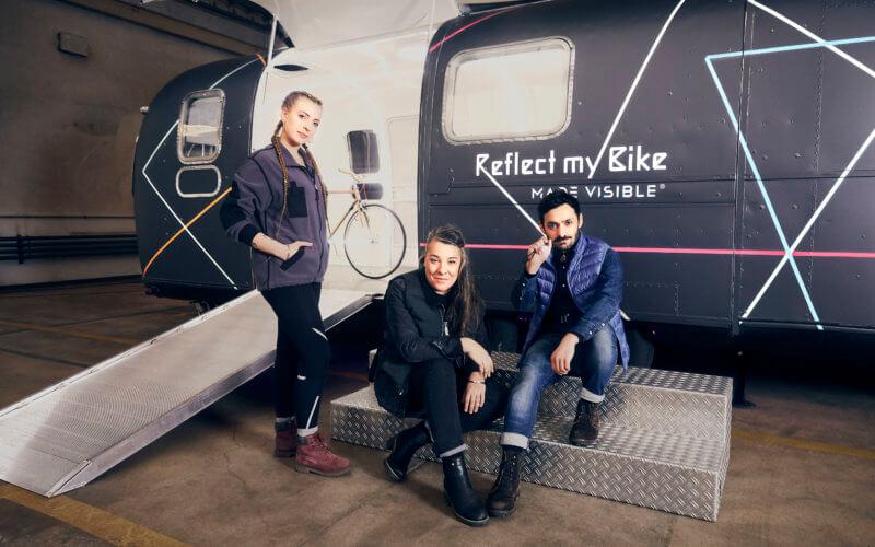Die Crew von Reflect my Bike präsentiert sich vor der mobilen Werkstatt: Links steht Velomechanikerin Camille, in der Mitte sitzt Designerin Tatjana und rechts Moderator Ali.