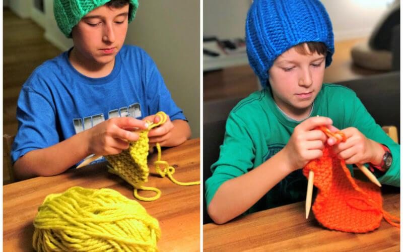 zwei junge Jungen stricken blaue und grüne Mütze am Esstisch
