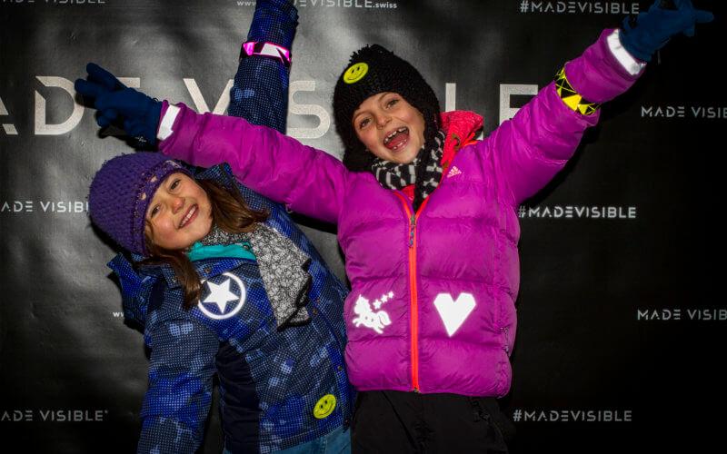 Zwei Mädchen präsentieren sich in ihren mit Reflektorfolien verzierten Jacken