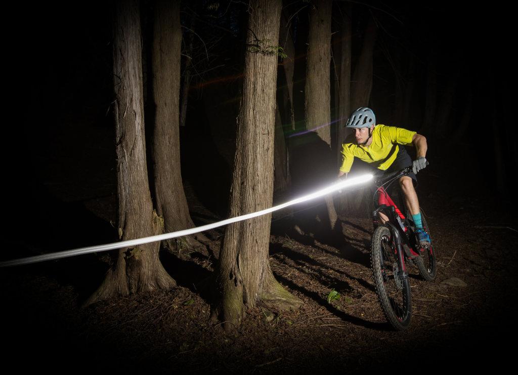 Montain Biker a cavallo nel bosco di notte utilizzando una forte luce bicicletta.
