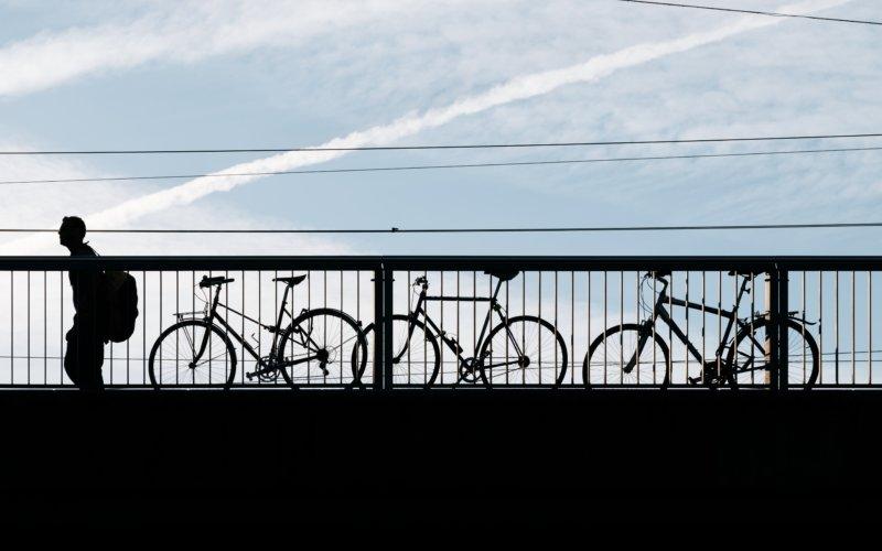 Silhouette eines Mannes mit einem Rucksack, der an drei Fahrrädern vorbeigeht, die an ein Brückengeländer gekettet sind.